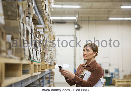 Manager using smart phone in warehouse - Stock Photo