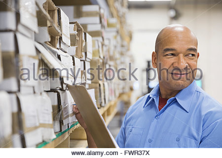 Male worker with clipboard in warehouse - Stock Photo