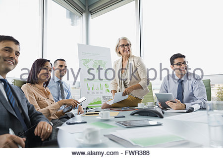 Business team smiling in boardroom - Stock Photo