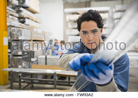 Male worker examining metal in warehouse - Stock Photo