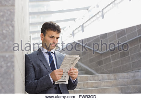 Businessman reading newspaper on steps - Stock Photo