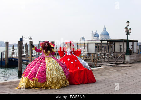 Two ladies in a traditional Venetian carnival dress and masks, at Piazza San Marco. - Stock Photo