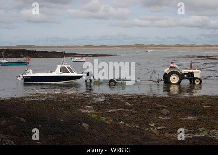 Two men prepare a small fishing boat to be taken out of the sea on a launch trolley being towed by a white David - Stock Photo