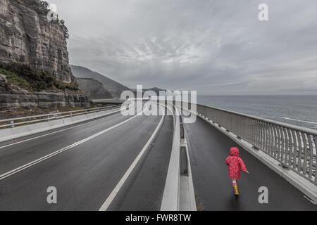 Child running on Sea Cliff Bridge, Grand Pacific Drive, Sydney, Australia - Stock Photo