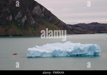 Small boat beside an iceberg in Krossfjorden. - Stock Photo