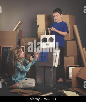 Children are building a metal robot from cardboard boxes with tools and books for an imagination, science or education - Stock Photo