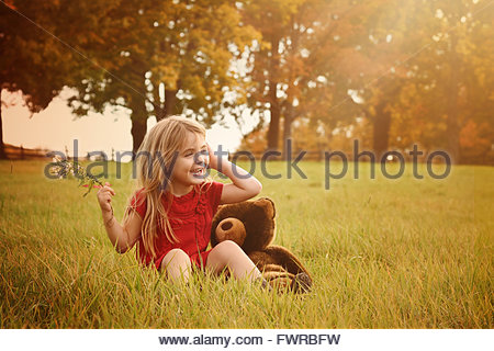 A little girl is sitting outside in the country with green grass and sunshine for a happiness or nature concept. - Stock Photo