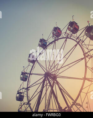 A Ferris wheel is spinning at a carnival at sunset for an artistic activity or summer memory concept. - Stock Photo