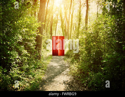 A red doorway is on a trail in the woods with trees for a conceptual concept about faith, freedom or freedom concept. - Stock Photo