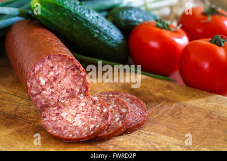 Sujuk sausage on wooden cutting board with fresh vegetables in background. Copy space - Stock Photo