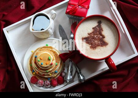 Christmas Breakfast on a tray pancakes and Coffee with chocolate dusting - Stock Photo