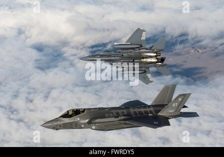 A U.S. Air Force  F-35 Lightning II fighter aircraft and an F-15E Strike Eagle fighter fly over the range near Mountain - Stock Photo