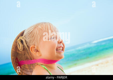 On sunny white sand beach happy smiling baby girl with vietnamese straw hat on head has fun before swimming in sea - Stock Photo