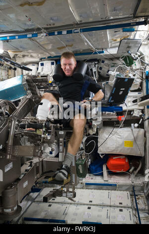 British astronaut Tim Peake with the European Space Agency operates the Muscle Atrophy Research and Exercise System - Stock Photo