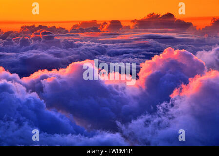 view over the clouds at sunrise from Haleakala crater on Maui - Stock Photo