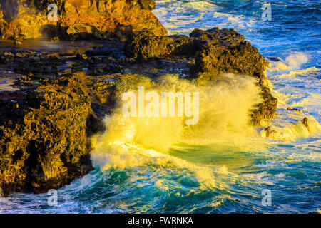 North shore Maui waves breaking against volcanic rock sea cliffs - Stock Photo