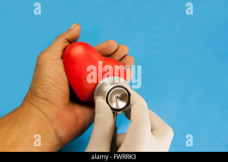 heart check up by stethoscope. red heart ceramic in hand on blue fabric background. With Clipping Paths. - Stock Photo