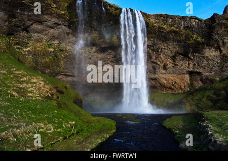 Seljalandsfoss waterfall with hikers on trail leading behind the fall, Iceland - Stock Photo
