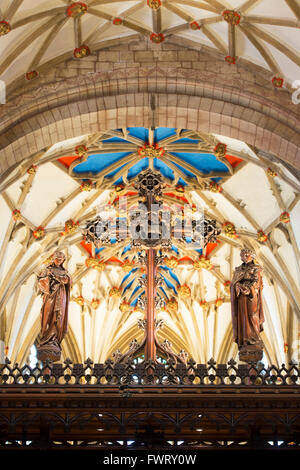 Wooden cross in front of the decorated vaulted ceiling in Tewkesbury Abbey. Tewkesbury, Gloucestershire, England. - Stock Photo