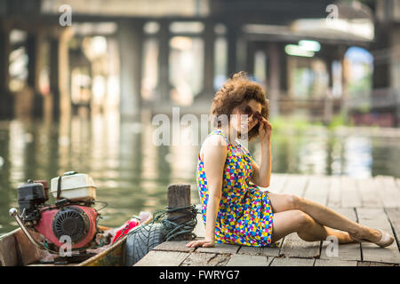 Fashionable asian woman sitting on a wooden river pier. - Stock Photo