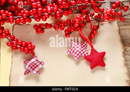 Ilex verticillata (winterberry) and red stars on vintage paper background. - Stock Photo
