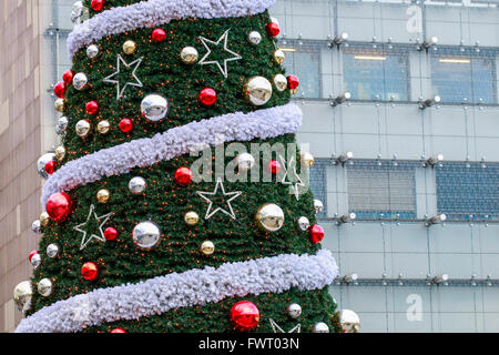 Traditional big christmas tree in front of modern building. Xmas decor - Stock Photo