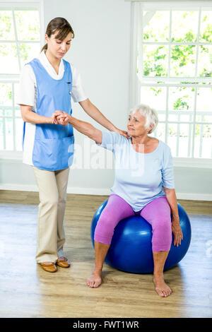 Senior woman exercising with nurse - Stock Photo