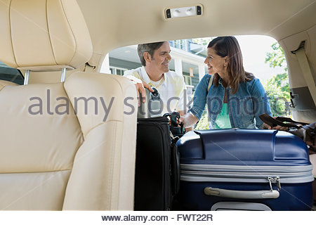 Smiling couple loading luggage into minivan - Stock Photo