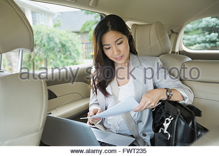 Businesswoman reviewing documents in car - Stock Photo