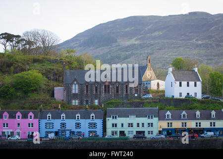 A view of the colourful shops and church of Portree harbour on the Isle of Skye in Scotland. - Stock Photo