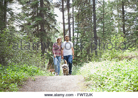 Happy couple taking dog for walk in forest - Stock Photo