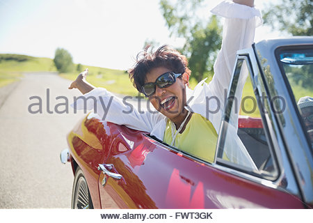 Portrait of excited middle-aged woman in red convertible - Stock Photo