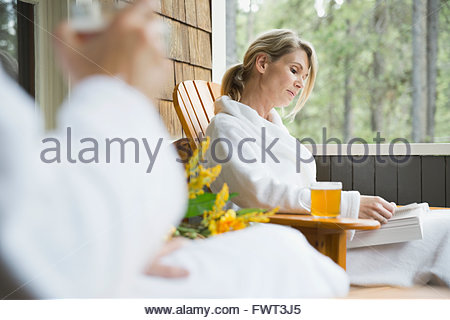 Middle-aged woman reading book on porch - Stock Photo