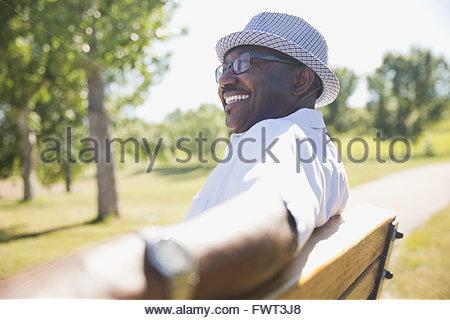 Smiling senior man sitting on park bench - Stock Photo
