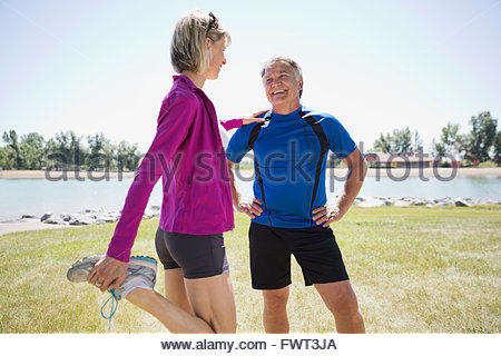 Active middle-aged couple stretching by the beach - Stock Photo