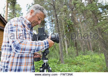 Man adjusting lens of SLR camera in yard - Stock Photo
