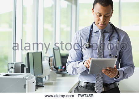 Young male doctor using digital tablet in radiology center - Stock Photo
