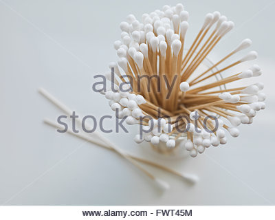 Cotton swabs in container on white background - Stock Photo