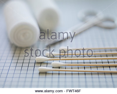 Cotton swabs and bandages on table - Stock Photo