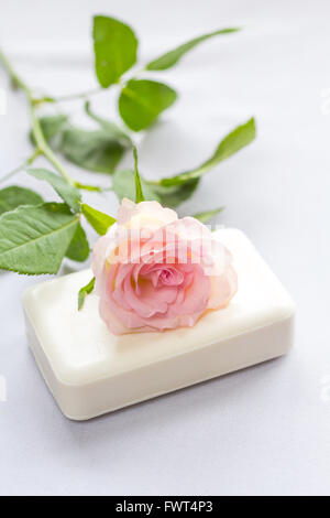 Beautiful, pink rose on a piece of white soap - Stock Photo