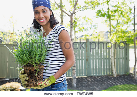 Pretty mid adult woman holding plant outdoors - Stock Photo