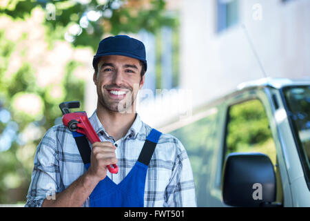 Portrait of happy carpenter holding pipe wrench - Stock Photo
