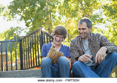 Happy father looking at son wearing baseball glove in yard - Stock Photo
