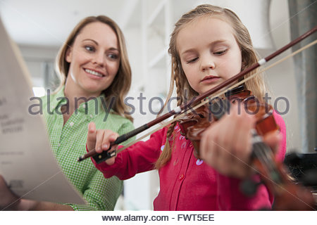 Mother holding music sheet while daughter practices violin at home - Stock Photo