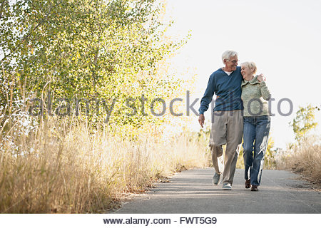 Happy senior couple walking on pathway in park - Stock Photo