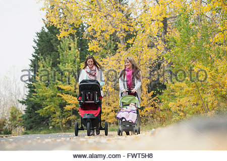 Mothers pushing babies in strollers on pathway - Stock Photo