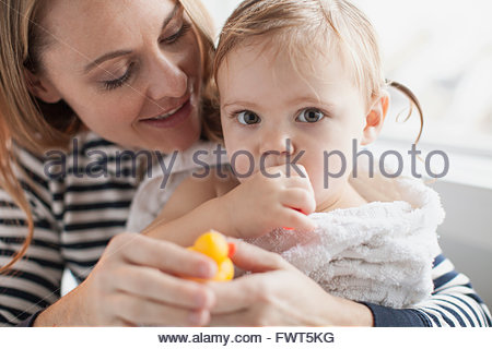 Mother holding baby girl wrapped in towel after bath - Stock Photo