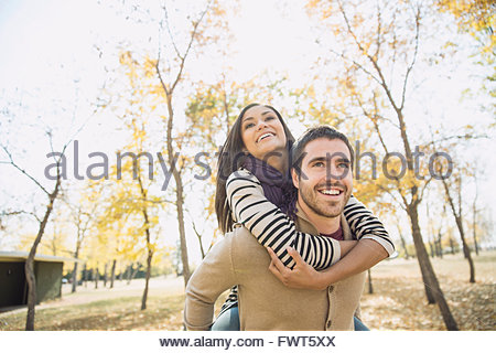 Young man giving woman piggyback ride in park - Stock Photo