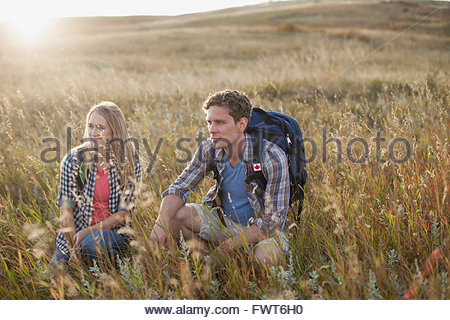 Couple crouching in grassy field. - Stock Photo