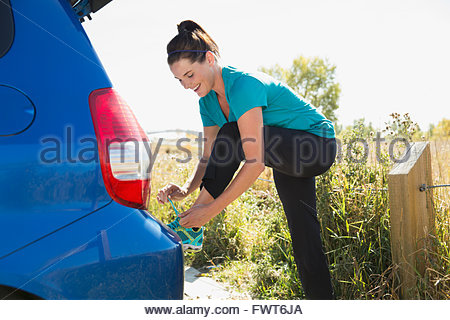 Woman tying up running shoes outdoors. - Stock Photo